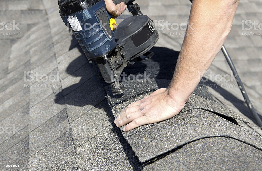 Installing Shingles over Ridge Vent stock photo