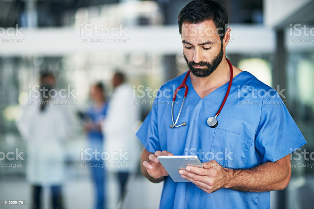 Installing the latest medical apps on his tablet stock photo