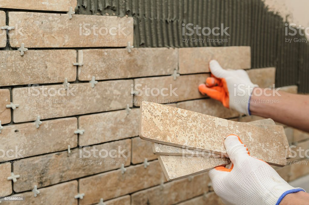 Installing the tiles on the wall. stock photo