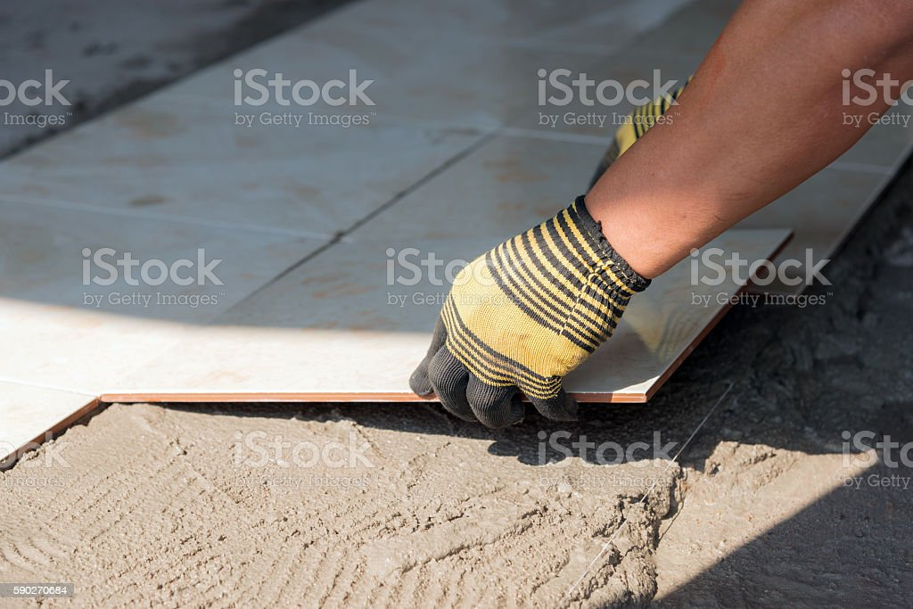 Installing tiles floor in construction work stock photo