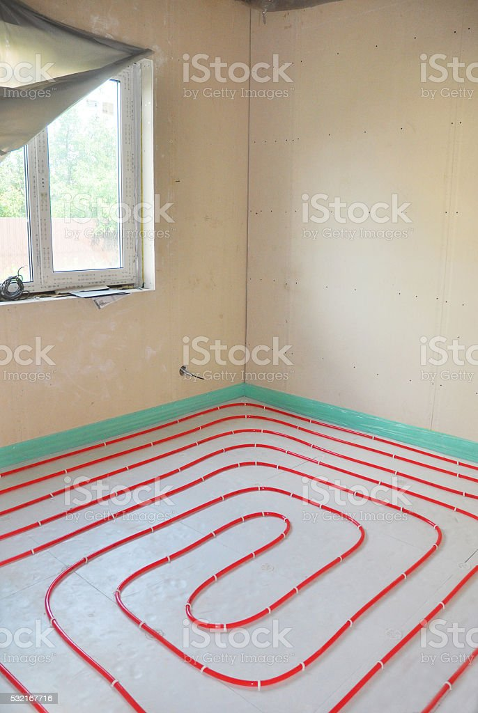 Installing water floor heating system stock photo