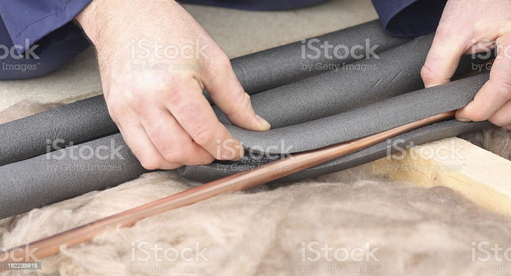 Installing water pipe insulation. stock photo