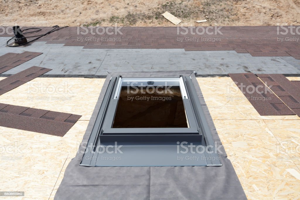 Installing window skylight on a roof with Asphalt Shingles or Bitumen Tiles under construction stock photo