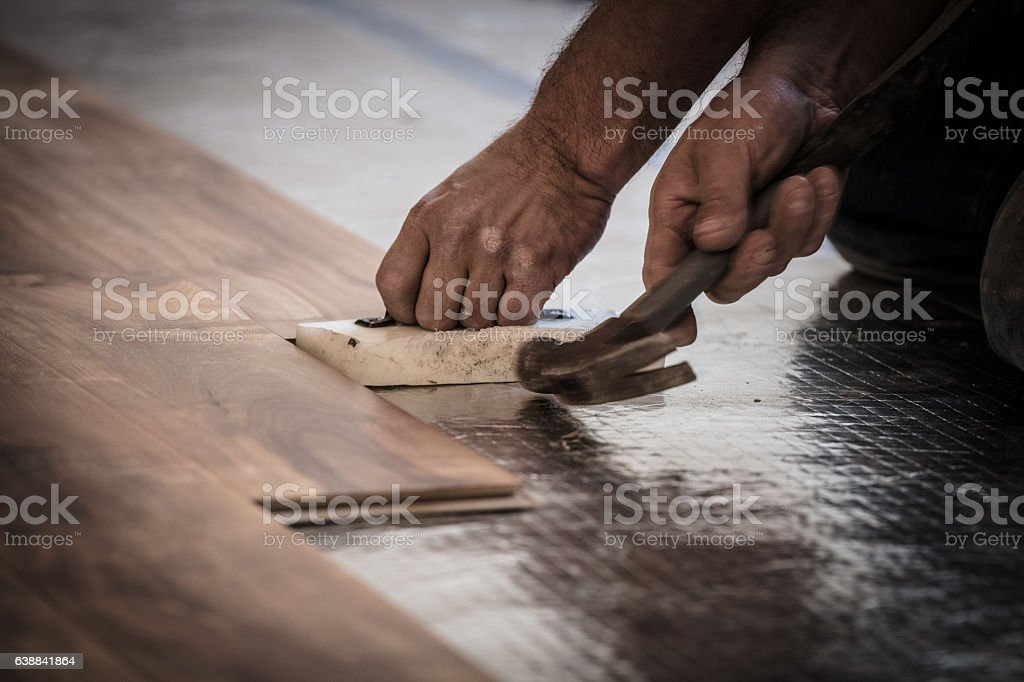 Installing Wood Flooring - Hammering stock photo