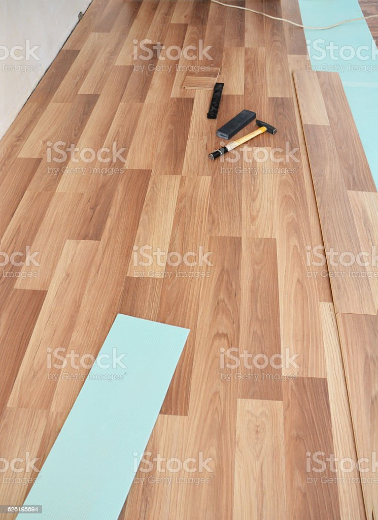Installing wooden laminate flooring with tools. stock photo
