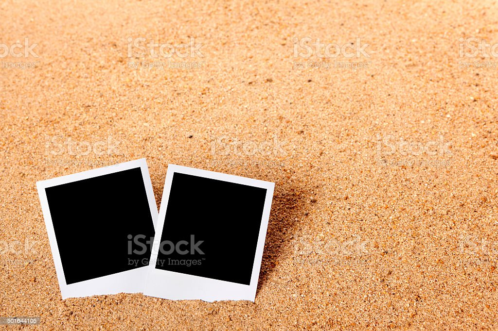 Instant camera prints on a sandy beach royalty-free stock photo