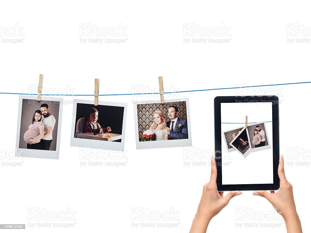 Instant photo prints hanged on string and digital tablet stock photo
