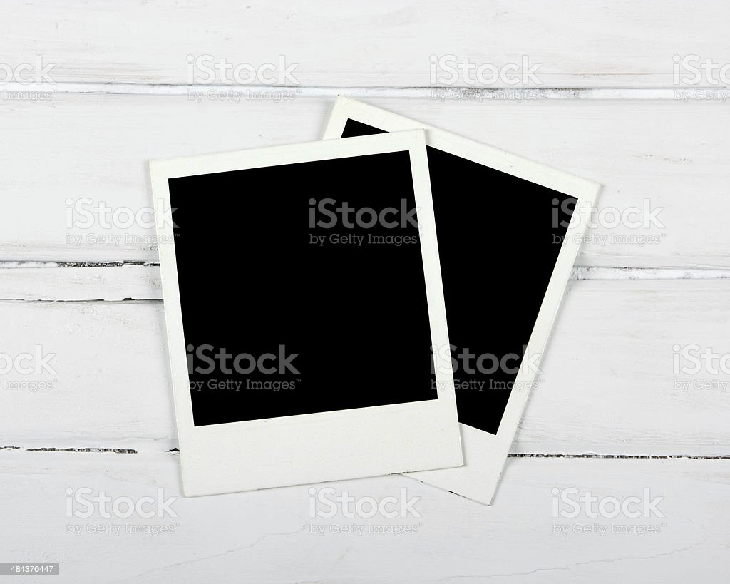 Instant photos on wooden table stock photo