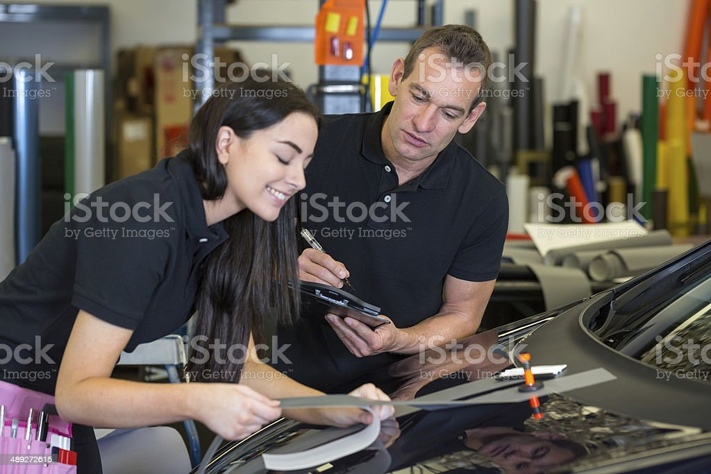 Instructor and apprentice in car wrapping workshop stock photo