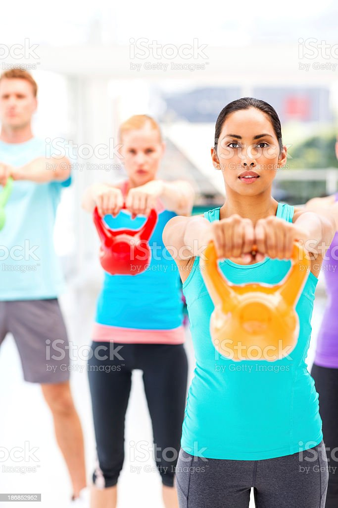 Instructor And Customers Exercising With Kettle Bells In Health royalty-free stock photo