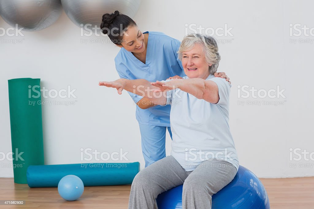 Instructor assisting senior woman in exercising stock photo