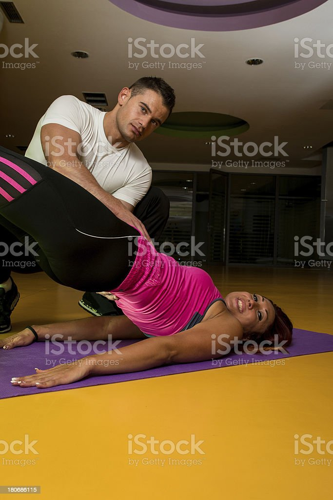 Instructor Assisting Woman In Doing Sit-Ups At Gym royalty-free stock photo