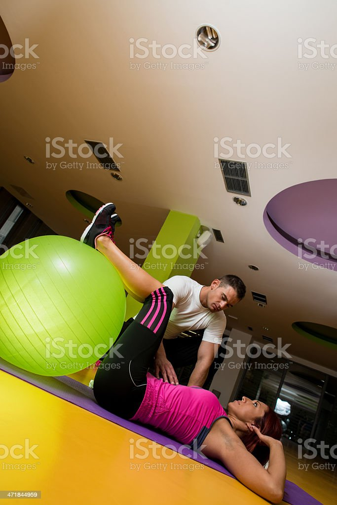 Instructor helping a woman with pilates exercises royalty-free stock photo