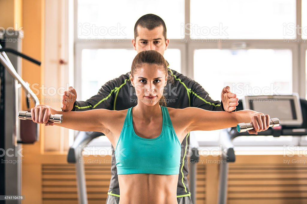 Instructor helping a young woman lift dumbbells in a gym stock photo