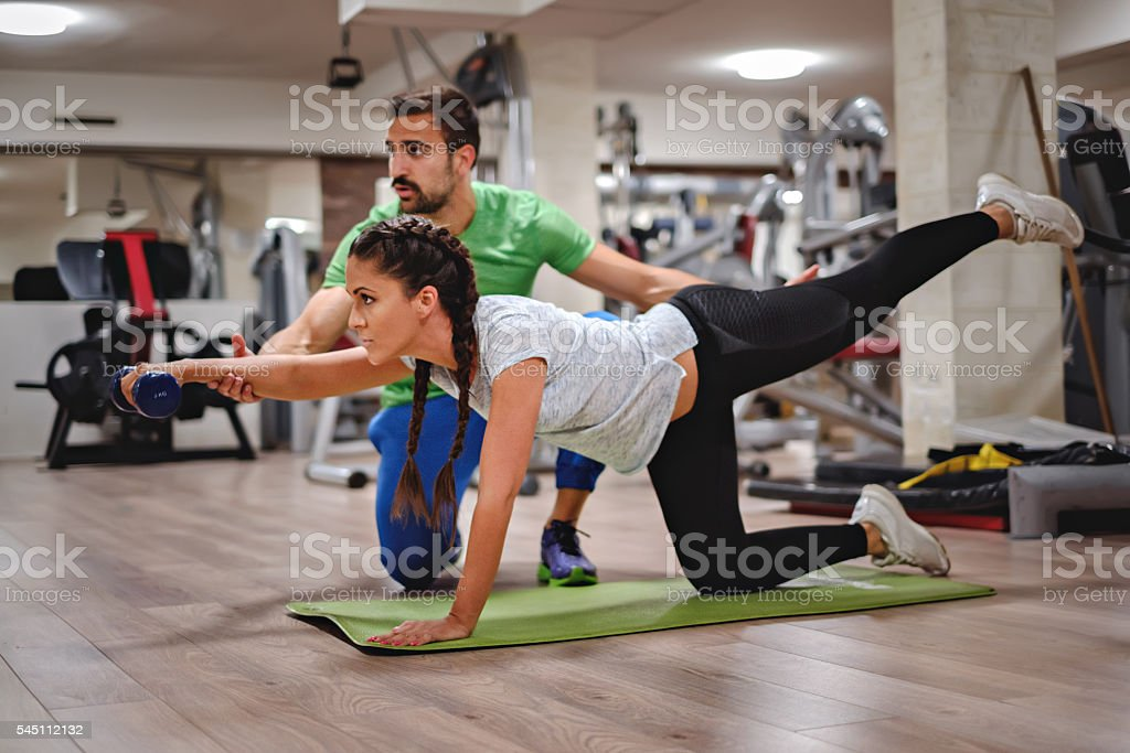 Instructor helping girl doing legs and shoulders stock photo