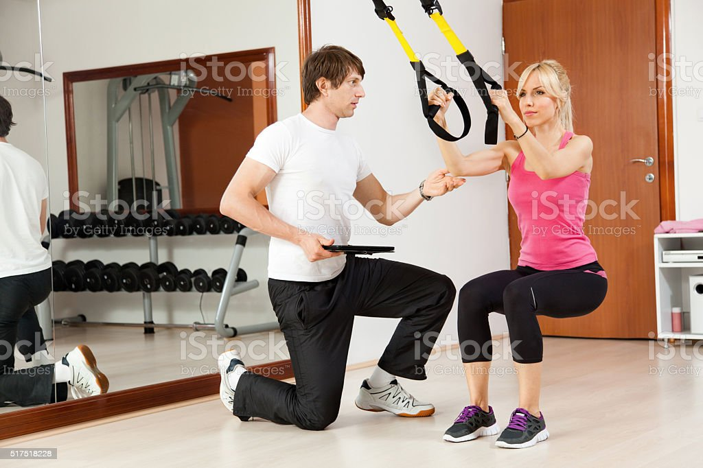 Instructor helping young woman with exercises in a gym. stock photo