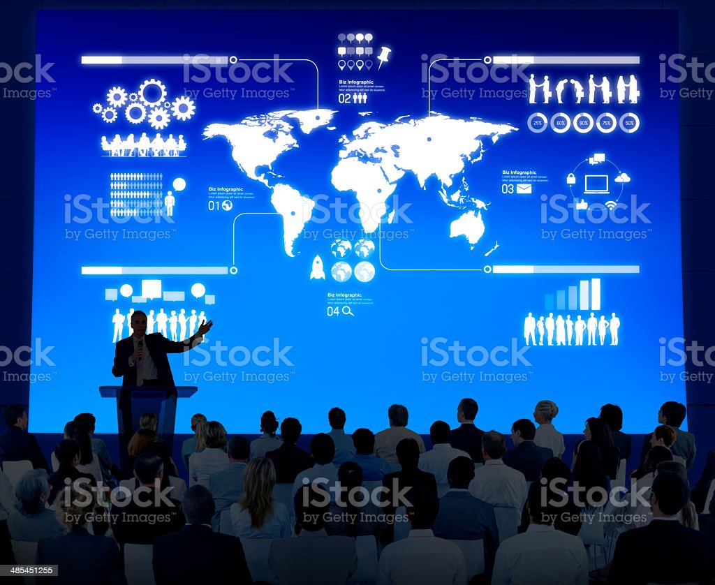 Instructor lectures to a crowd of businesspeople stock photo