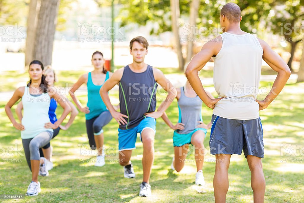 Instructor Looking At People Doing Lunges In Park stock photo