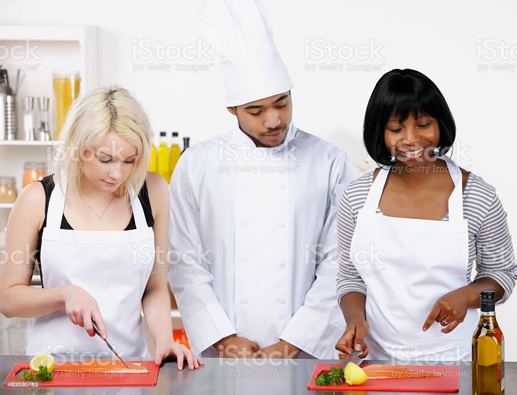 Instructor Observing Appentices/ Students Preparing Fish In A Commercial Kitchen royalty-free stock photo