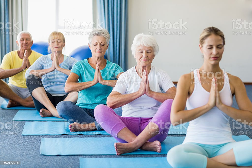Instructor performing yoga with seniors stock photo