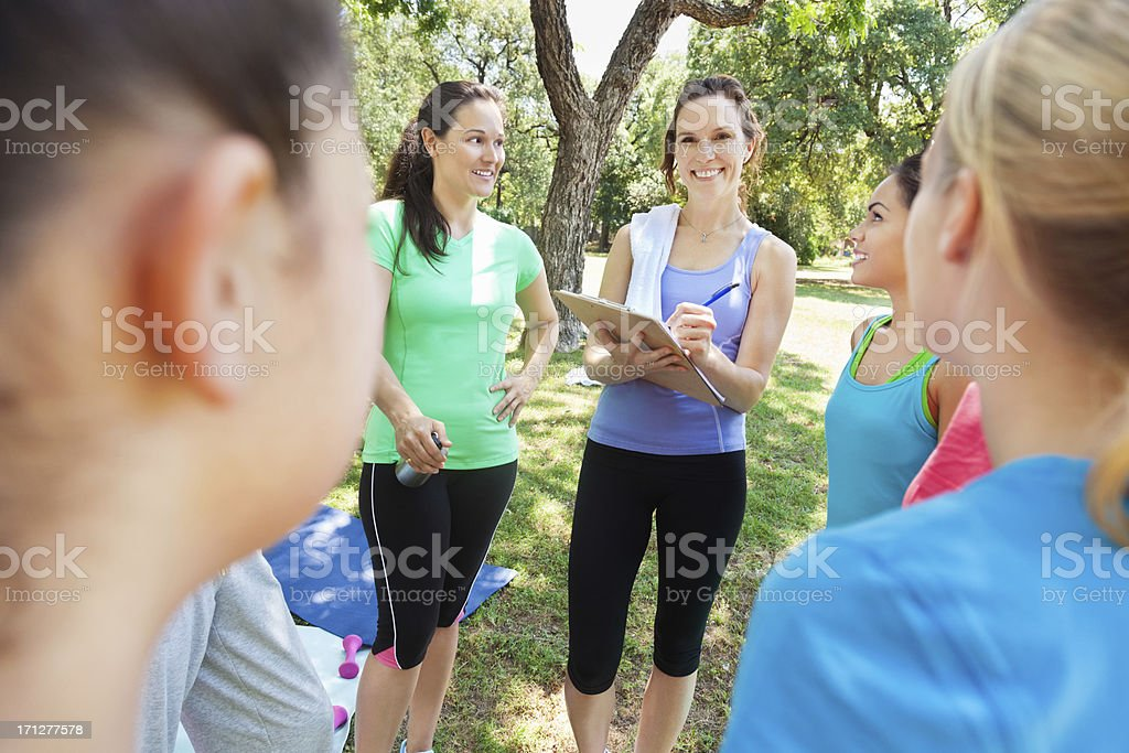 Instructor taking attendance at an outdoor fitness class royalty-free stock photo