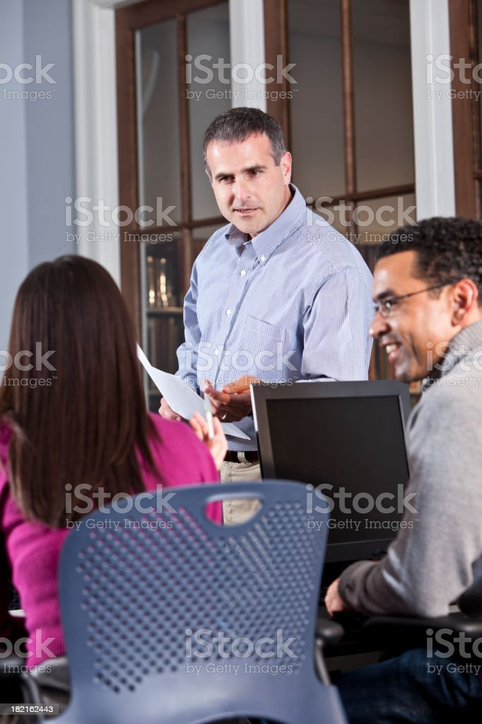 Instructor talking with continuing education students stock photo