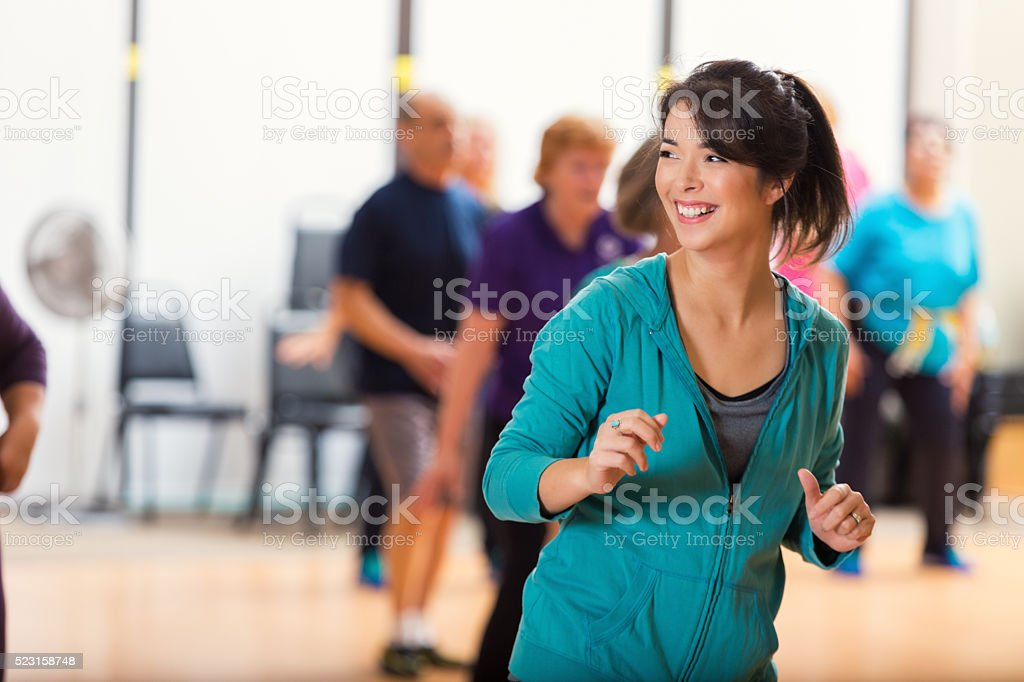 Pretty senior Caucasian female dance instructor teaches as group of...