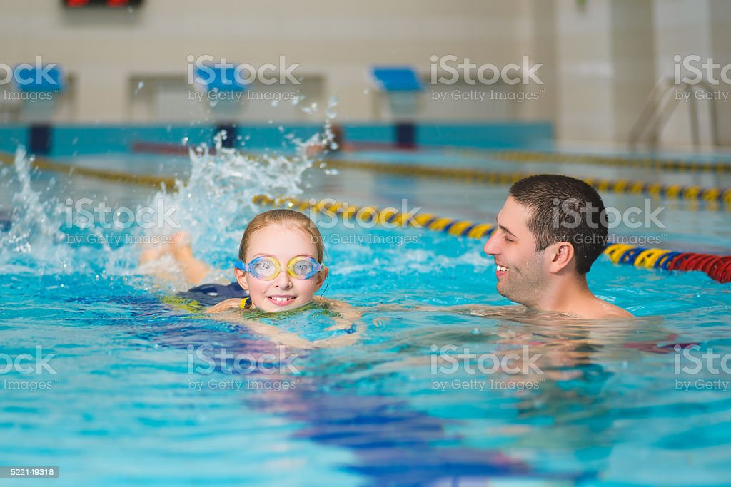 instructor teaches the girl swimming in a pool stock photo