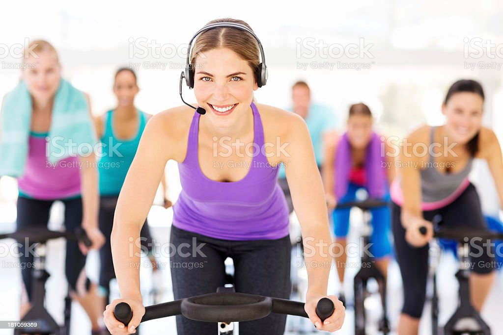 Instructor Wearing Headset With Cycling Class At Health Club royalty-free stock photo