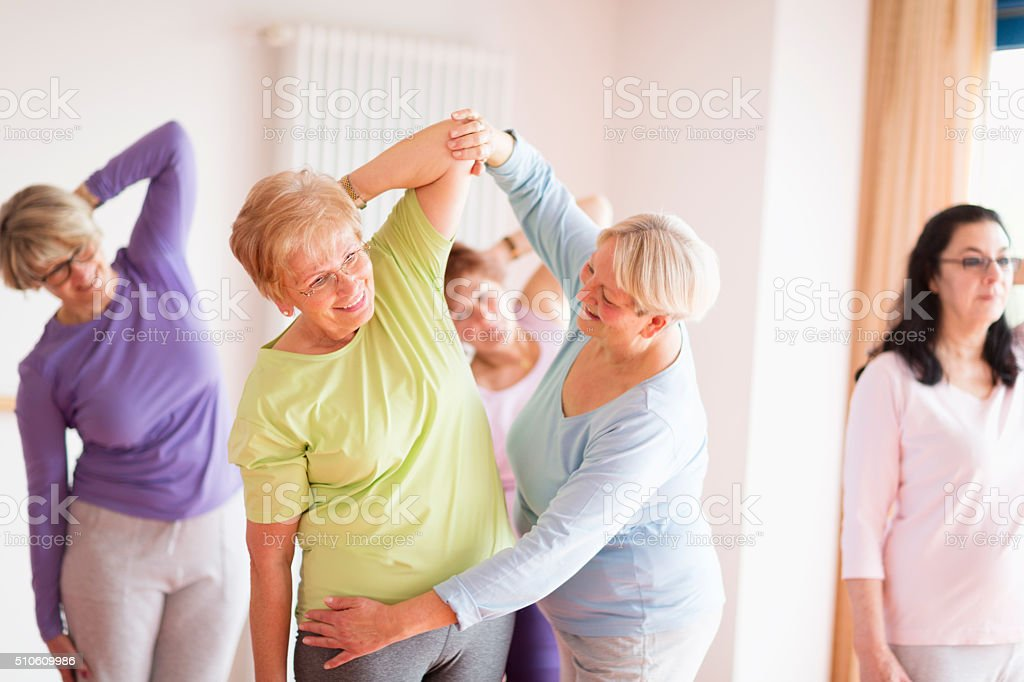 instructor with active senior women in yoga class stock photo