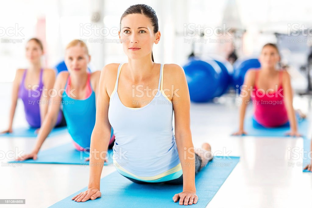 Instructor With Customers Doing Yoga Exercise In Health Club stock photo