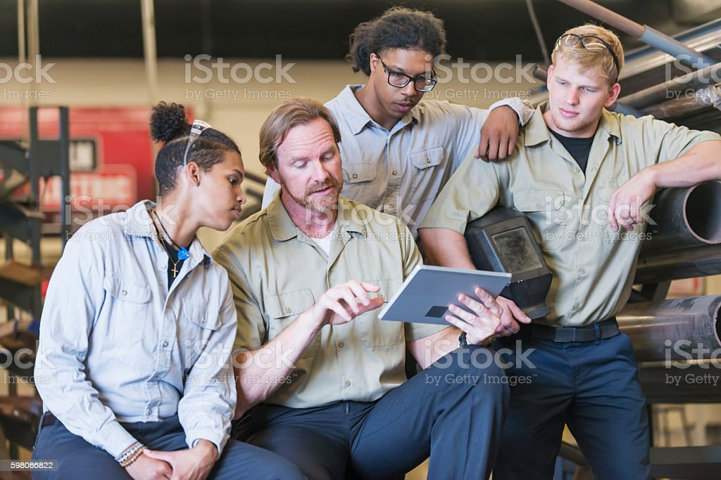 Instructor with trainees in welding school stock photo