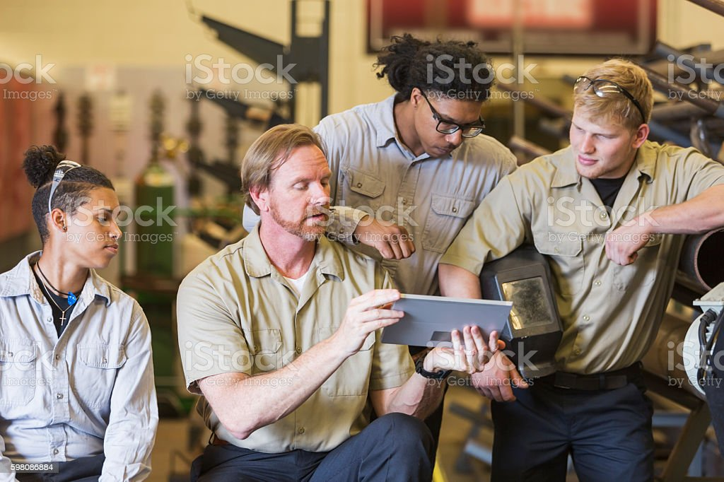 Instuctor and students in technical training school stock photo