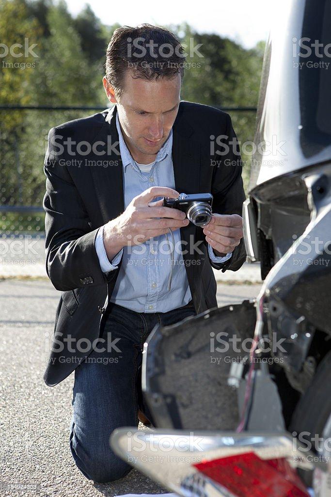 Insurance adjuster examining damage to car exterior stock photo