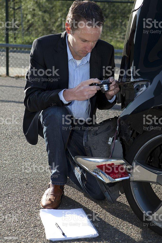Insurance adjuster looking at damaged car royalty-free stock photo