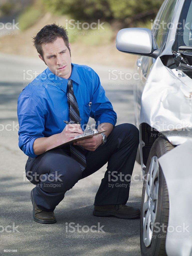 Insurance adjuster looking at damaged car stock photo