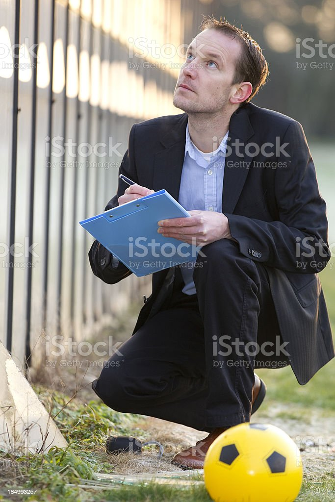 Insurance adjuster looking at damaged glass stock photo
