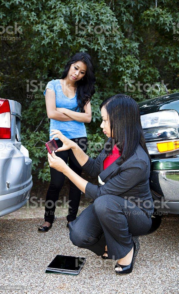 Insurance adjuster photographing damage to vehicle stock photo
