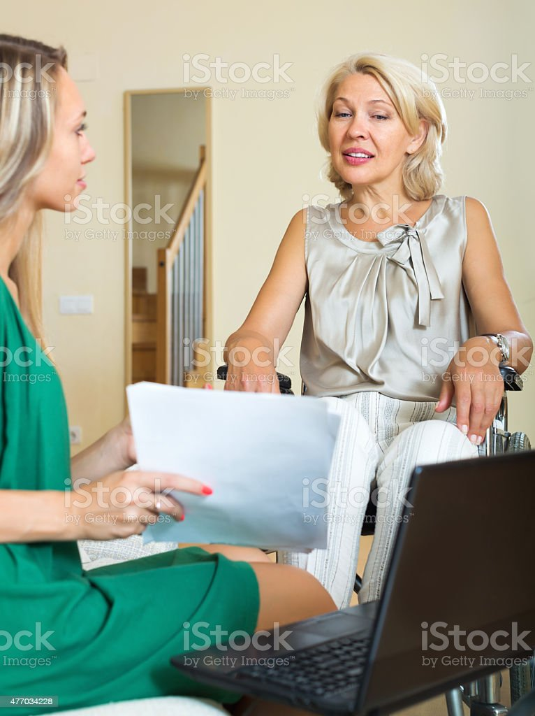 Insurance agent and disabled woman stock photo
