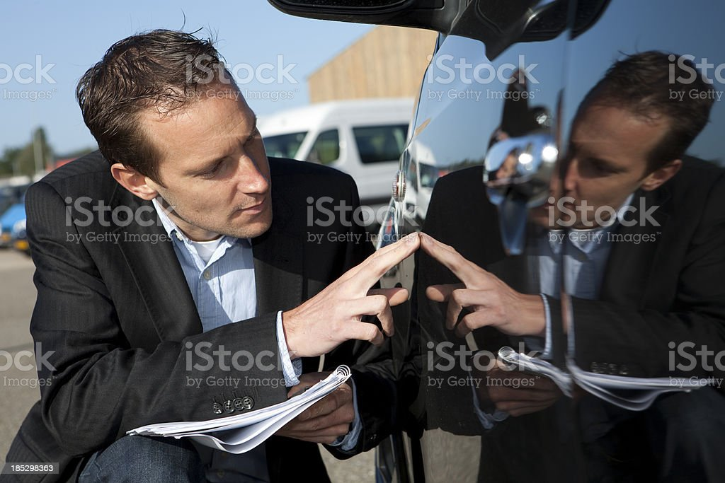 Insurance agent inspecting damage on a car stock photo