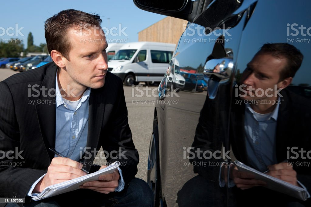 Insurance agent looks at car stock photo