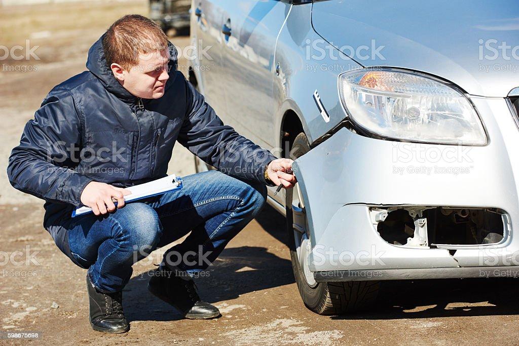 Insurance agent recording car damage on claim form stock photo