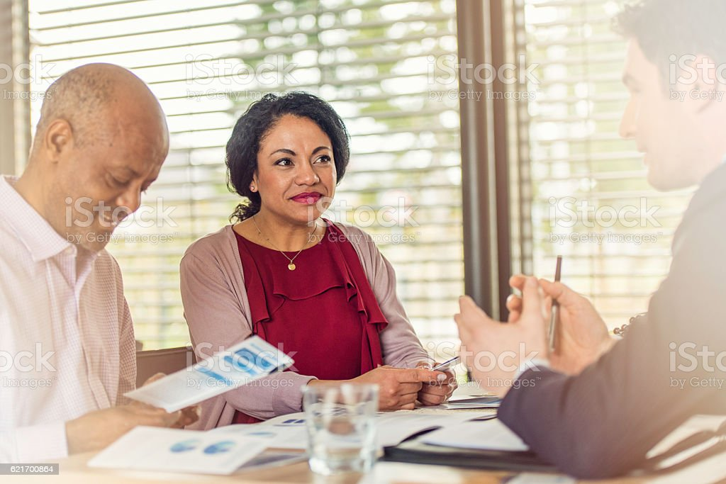 Insurance agent talking to older couple of african ethnicity stock photo