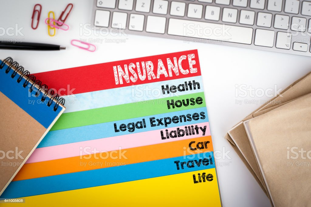 Insurance. Office desk with a computer keyboard and color pages stock photo