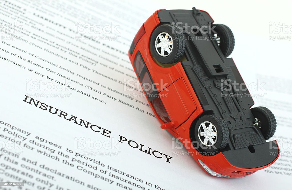 Insurance Policy with overturned car stock photo