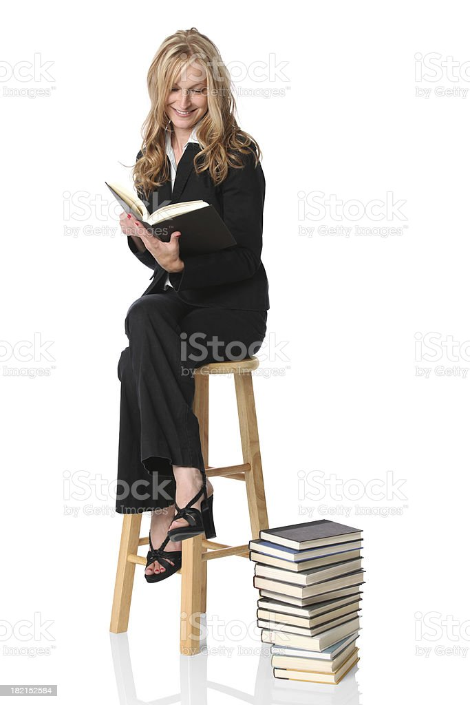 Intellectual young businesswoman studying a stack of books royalty-free stock photo