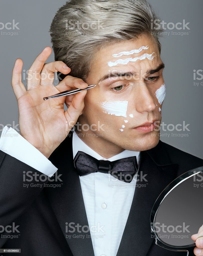 Intelligent and handsome man tweezing the hair on his face stock photo