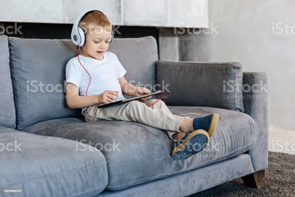 Intelligent savvy kid spending time with his gadget stock photo