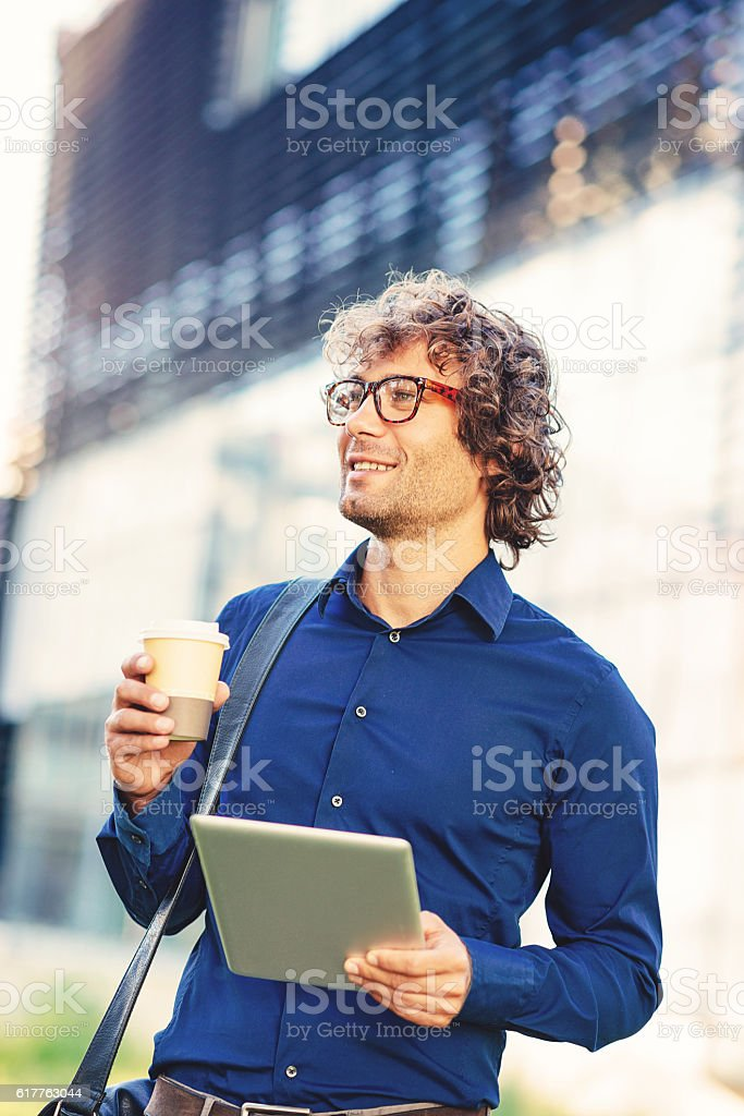 Intelligent young man with glasses using digital tablet stock photo