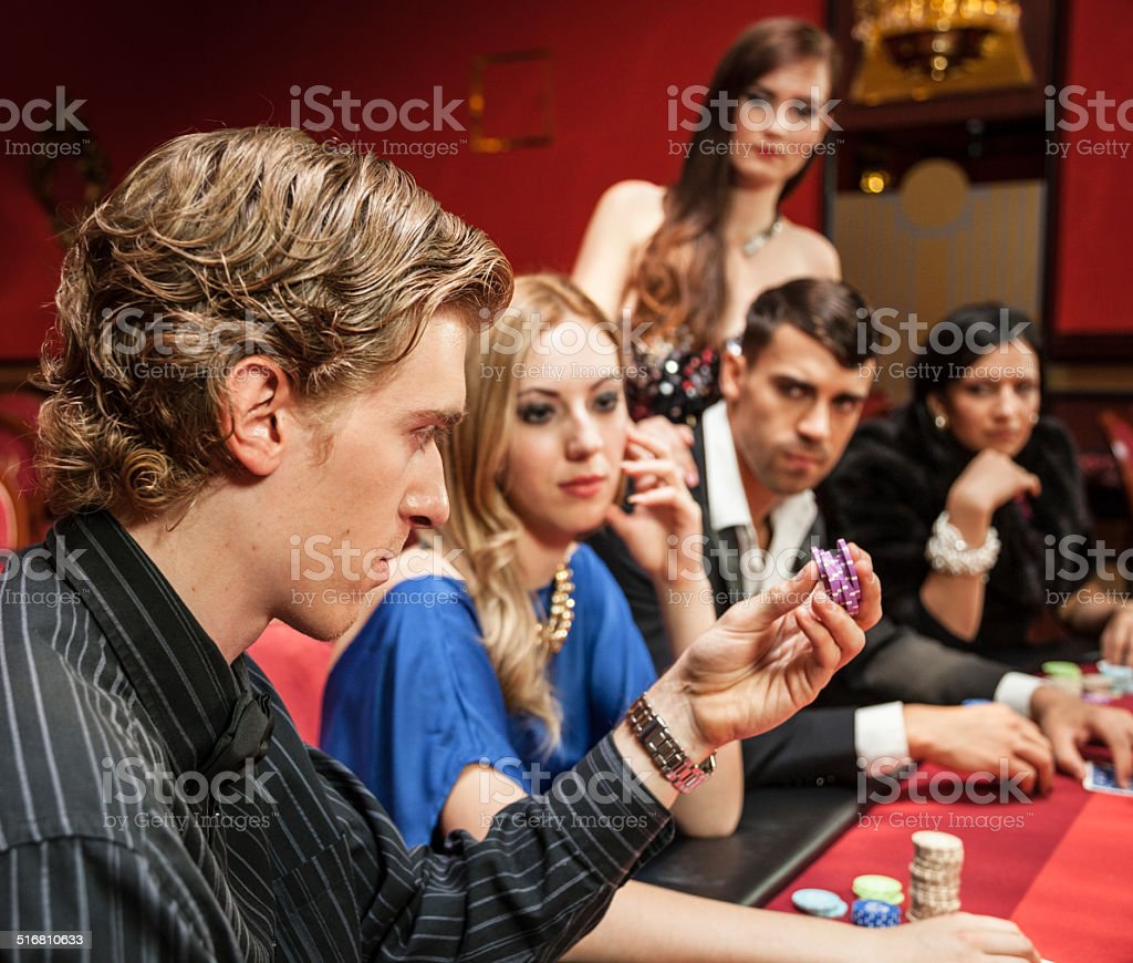 intense gamblers wait for man to bet in casino stock photo